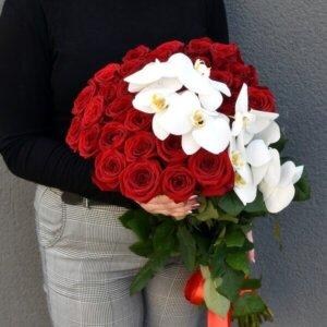 Raudonos rožės ir orchidėjos gėlės puokštėse